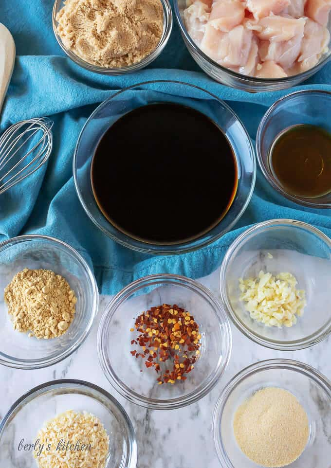 An aerial photo of the ingredients like red pepper flakes, soy sauce, and brown sugar in clear glass bowls.