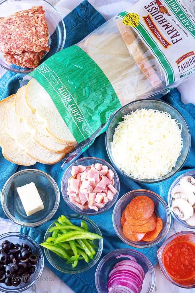 A top-down shot of the ingredients for the pizza grilled cheese, like red onion, pepperoni, and mushrooms.