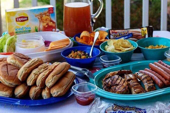 The finished backyard bash table setting with chicken breast, hot dogs, and iced tea.