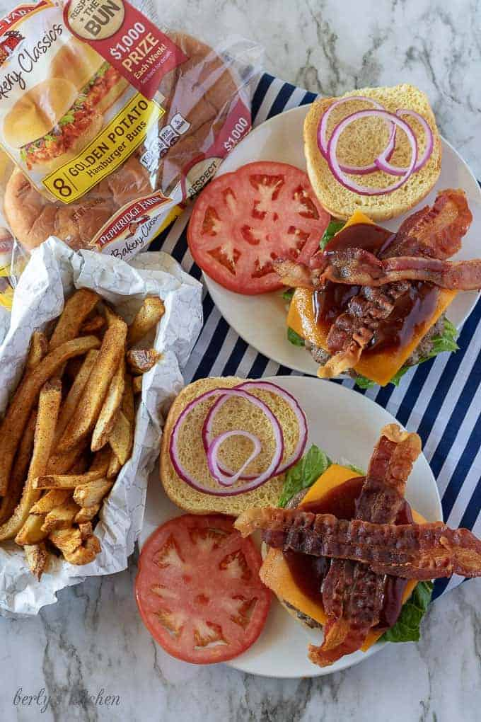 A top-down view of the bacon cheeseburgers being assembled with tomatoes, red onion, and BBQ sauce.