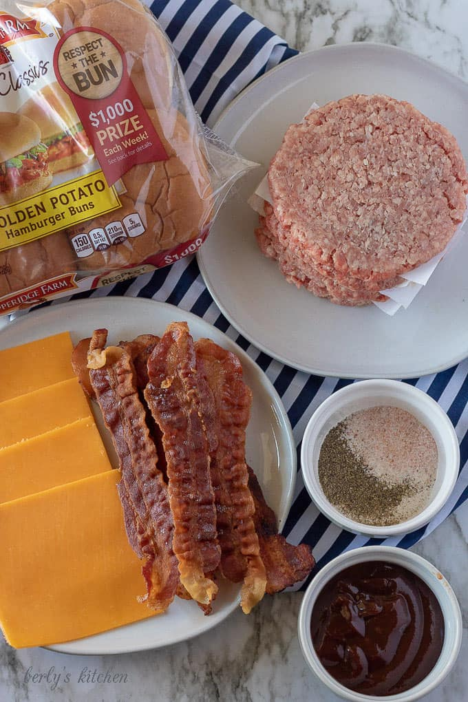 An aerial photo of the bacon cheeseburger ingredients like cheddar cheese, bacon slices, and all beef patties.