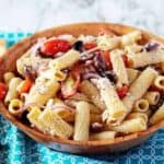 The finished Greek pasta salad in a wooden serving bowl on a blue towel.