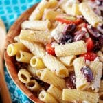 A close-up photo of the finished Greek pasta salad focused on the colors of the noodles, olives, tomatoes and red onions.