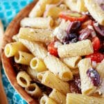 The finished, colorful Greek pasta salad in a wooden bowl on a blue towel.
