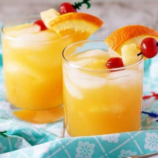 Two rum mixed drinks in tumbler glasses with orange, pineapple, and cherry garnishment.