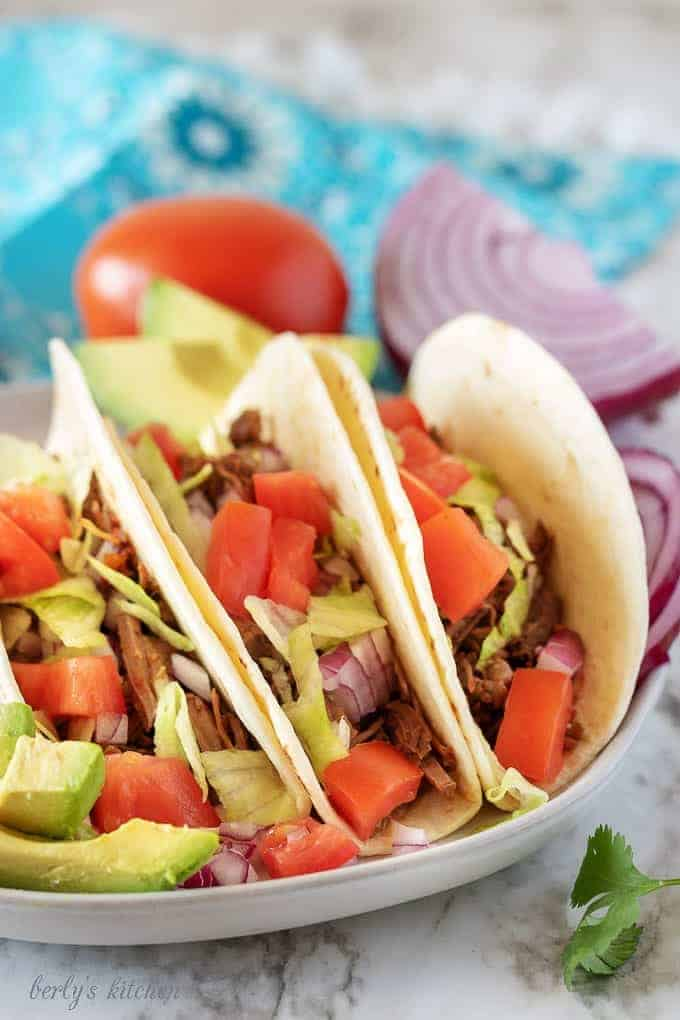 Three shredded beef tacos on a plate next to a tomato and purple onion.