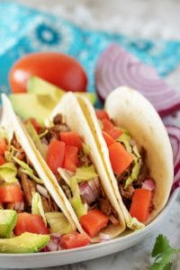 Shredded beef tacos on a grey plate used for Pinterest.
