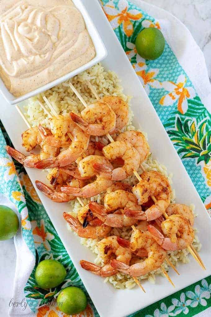 An aerial picture of the grilled shrimp skewers, over rice, with a square bowl of key lime aioli.