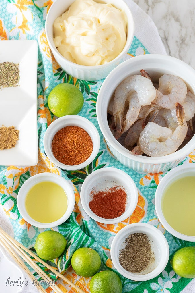 A photo displaying all the grilled shrimp ingredients like key lime juice, olive oil, seasonings in white bowls.