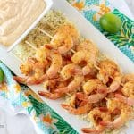 An aerial photo of the finished grilled shrimp on skewers, served over rice, on a rectangular white plate.