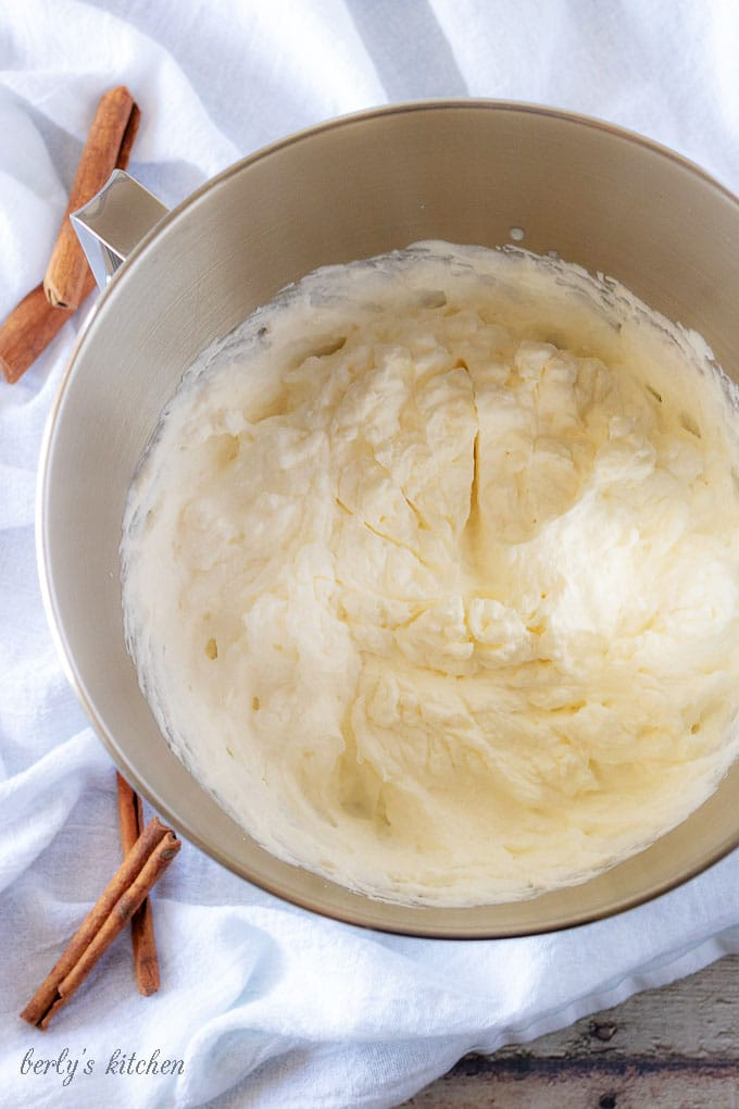 An aerial photo of the finished whipped cream in a mixing bowl showing stiff peaks of whipped cream.