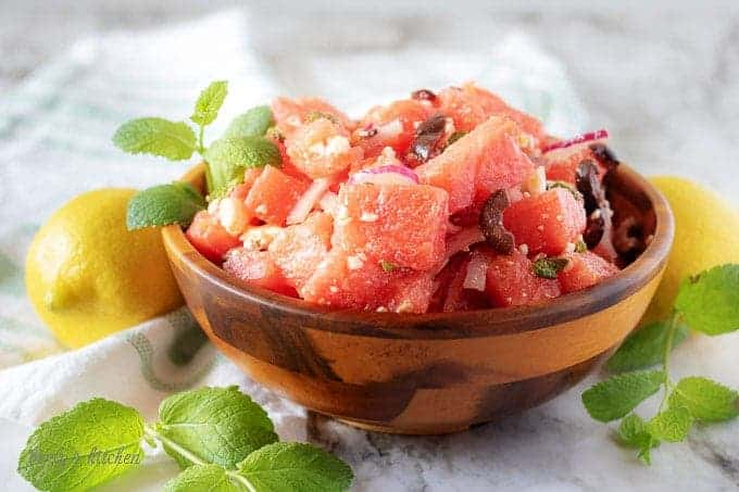 A small wooden bowl of watermelon salad, topped with fresh mint and crumbled feta cheese.