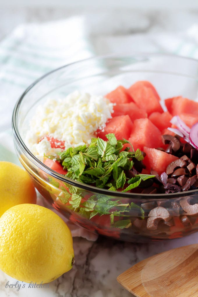 The watermelon salad ingredients, like red onion, fresh mint, feta cheese, and kalamata olives, in a glass mixing bowl.