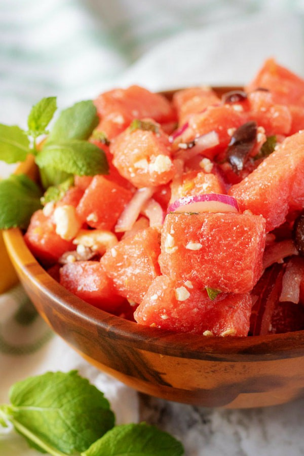 A close-up picture of the finished watermelon salad in a wooden serving bowl, garnished with mint.