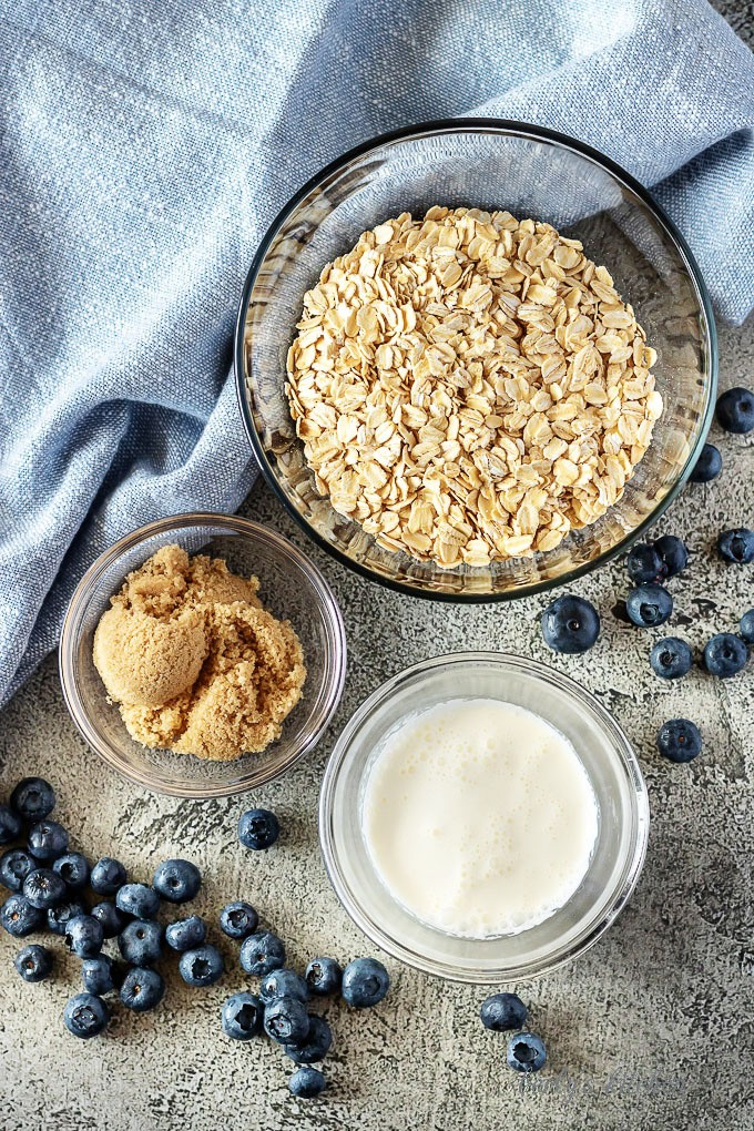 A top-down photo of the blueberry oatmeal ingredients like rolled oats, brown sugar, and fresh berries.