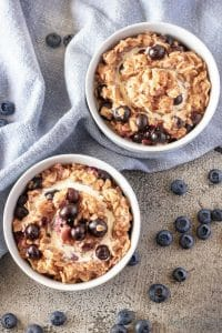 The blueberry oatmeal, top-down view, served in white bowls and garnished with fresh heavy cream and more blueberries.