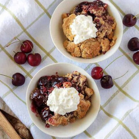 A top-down view of the cherry crisp in white bowls with whipped cream on top.