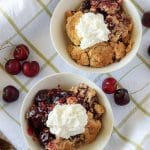 An aerial photo of the cherry crisp topped with whipped cream.