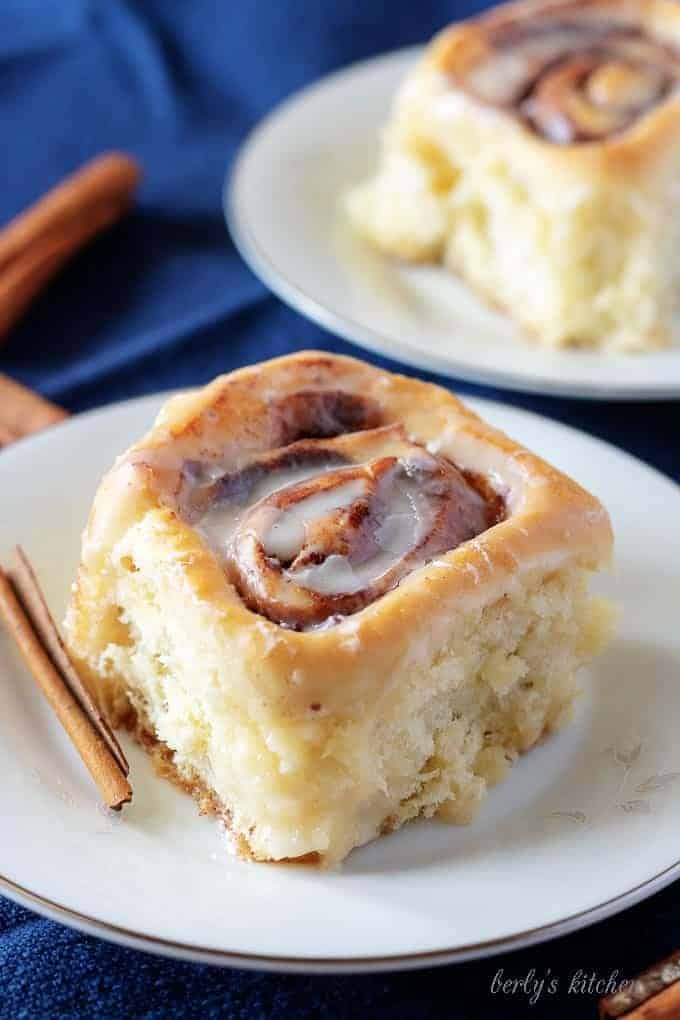 Homemade Cinnamon Rolls on white plates with cinnamon sticks and blue linens.