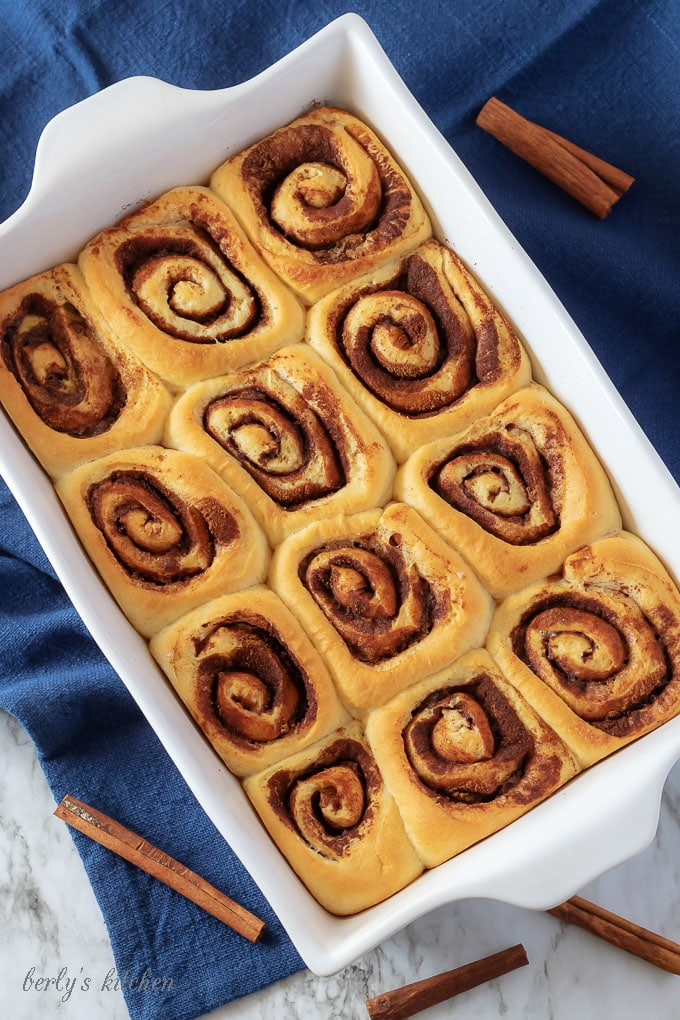 Ariel view of baked homemade cinnamon rolls in a white pan.