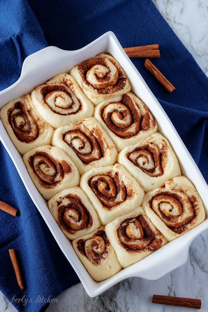 Ariel view of cinnamon rolls that have doubled in size in a white baking dish.