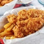 The homemade chicken tenders served with seasoned french fries served in red basket.