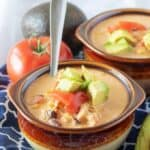 A close-up photo of the finished chicken taco soup in two earthenware bowls topped with diced tomatoes.