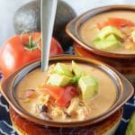 A large picture of the finished chicken taco soup in brown bowls and garnished with diced avocados and tomatoes.