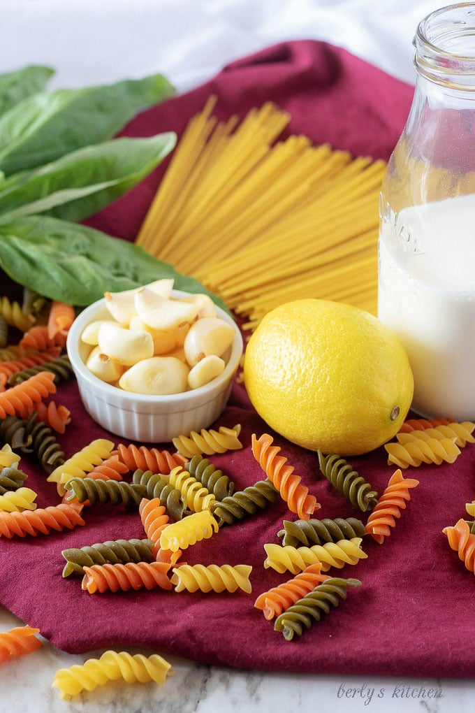 The lemon cream sauce ingredients, like fresh garlic and heavy cream with a fresh lemon surrounded by dry pasta.