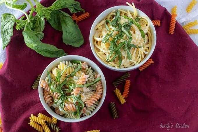 The finished lemon cream sauce served with tricolor rotini or spaghetti pasta in white bowls.