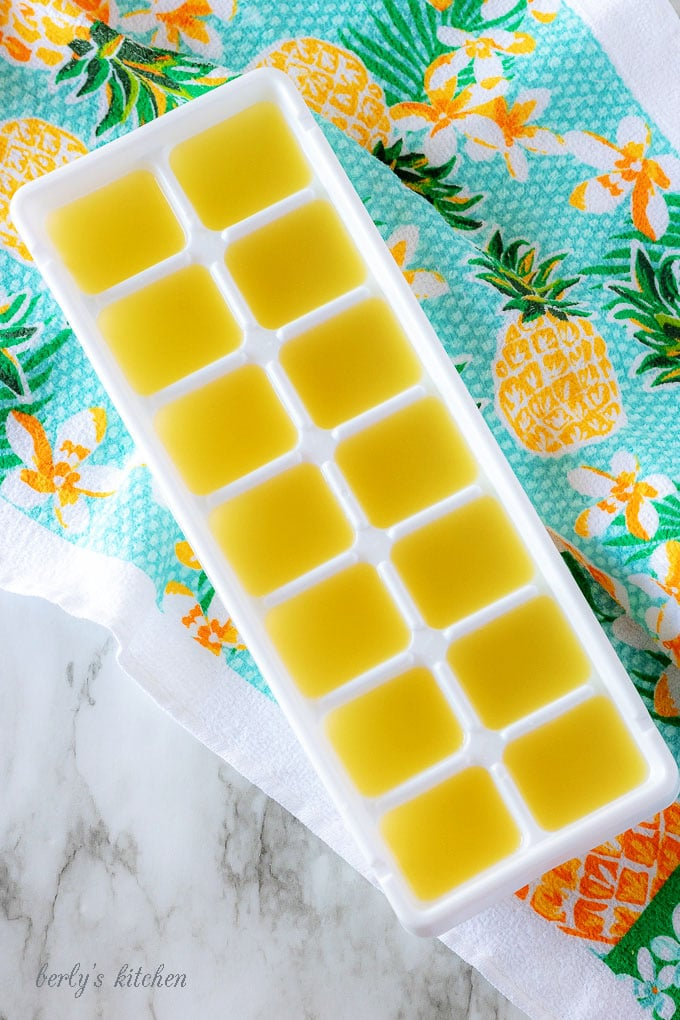The tropical cocktail mixture poured into a white ice cube tray for freezing.
