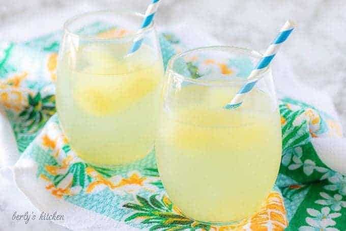 The finished tropical cocktail booze cubes, served with blue straws. As the cubes melt the water looks like lemonade.