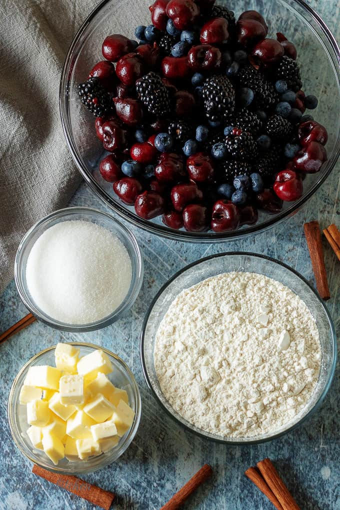A top-down photo of the berry cobbler ingredients like sugar, butter, flour, and mixed berries.