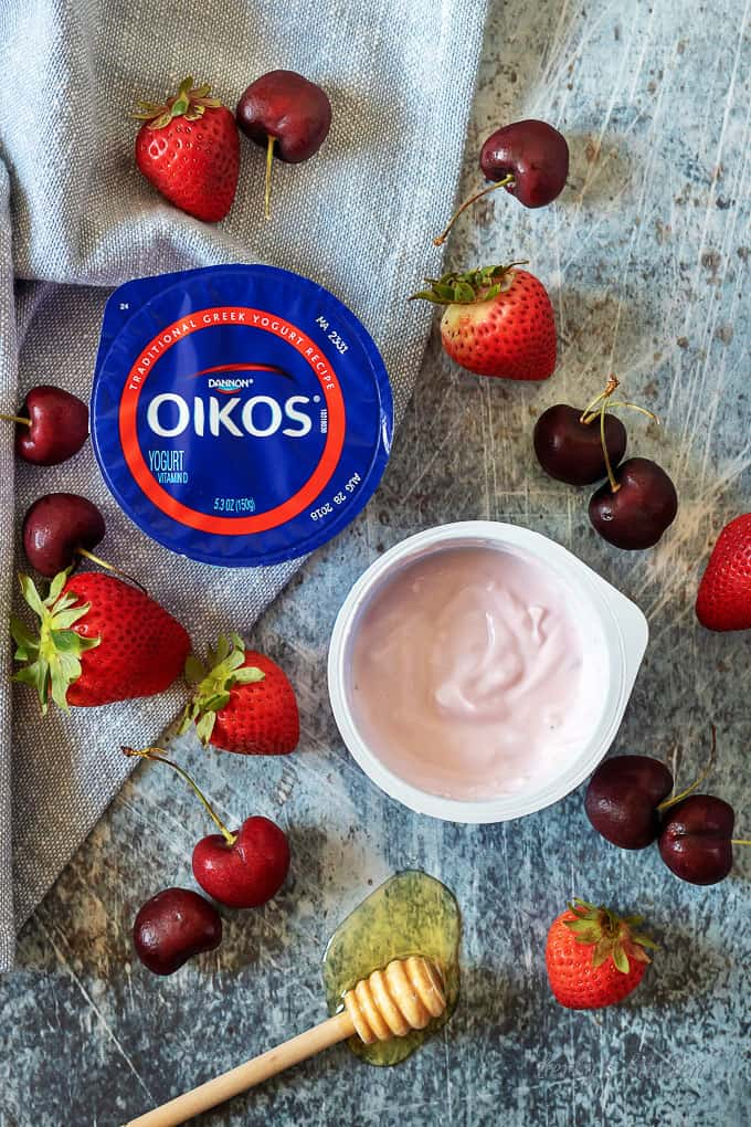 An aerial photo of the starwberry flavored greek yogurt along with the other berry smoothie ingredients.
