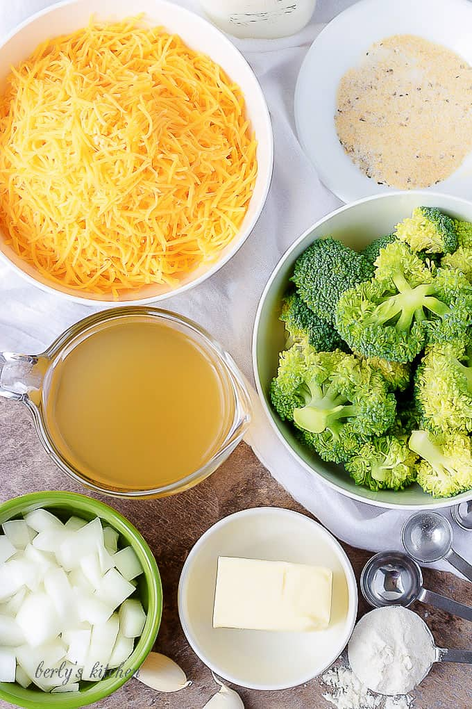 Ariel view of broccoli, cheese, broth, butter, onions, garlic, seasonings, and flour used for broccoli cheese soup.