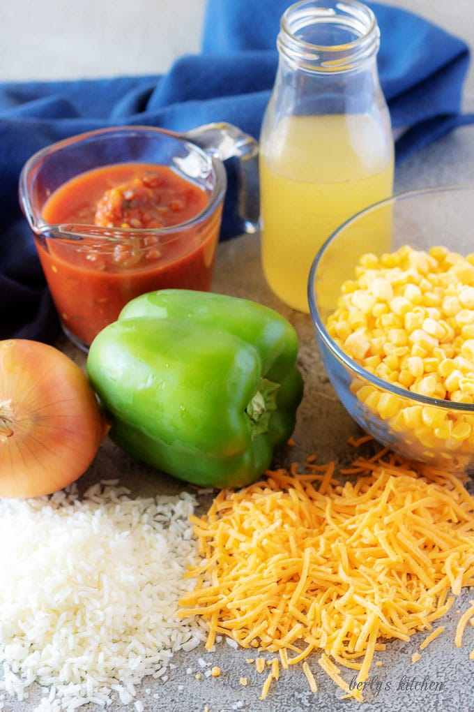 The Mexican rice ingredients like peppers, onions, salsa, corn, and cheddar cheese.