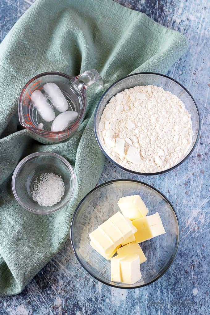 The homemade pie crust ingredients including flour, butter, salt, and iced water.