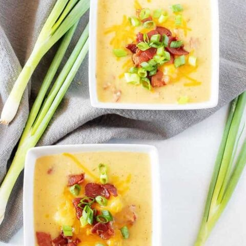 A final top-down picture if the finished instant pot potato soup with bacon served in two squares bowl.