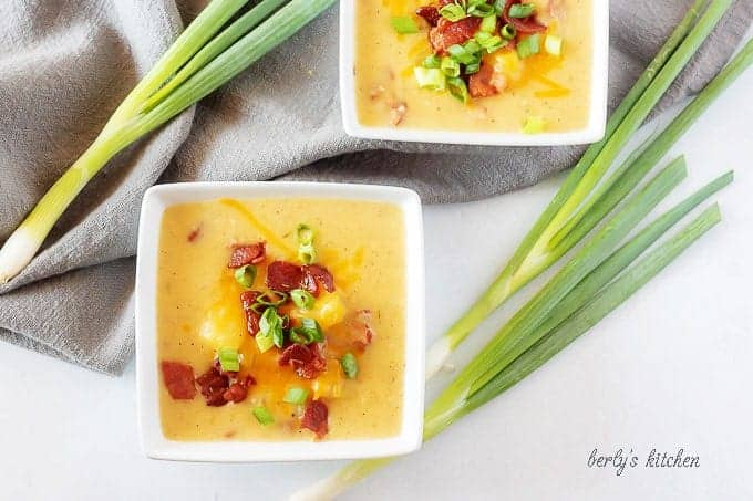 An aerial view of the potato soup with bacon in square bowls garnished with bacon and green onion.