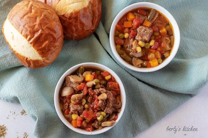 The finished vegetable beef soup in a white bowl and served with a pretzel roll.