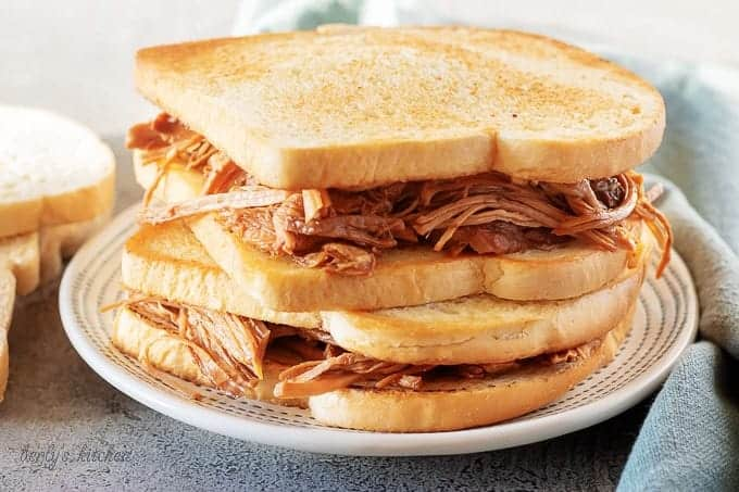 Two stacked pulled pork sandwiches, ready to be served on a white and green plate.