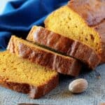The finished pumpkin bread recipe, showing one loaf with three even slices cut and falling over.