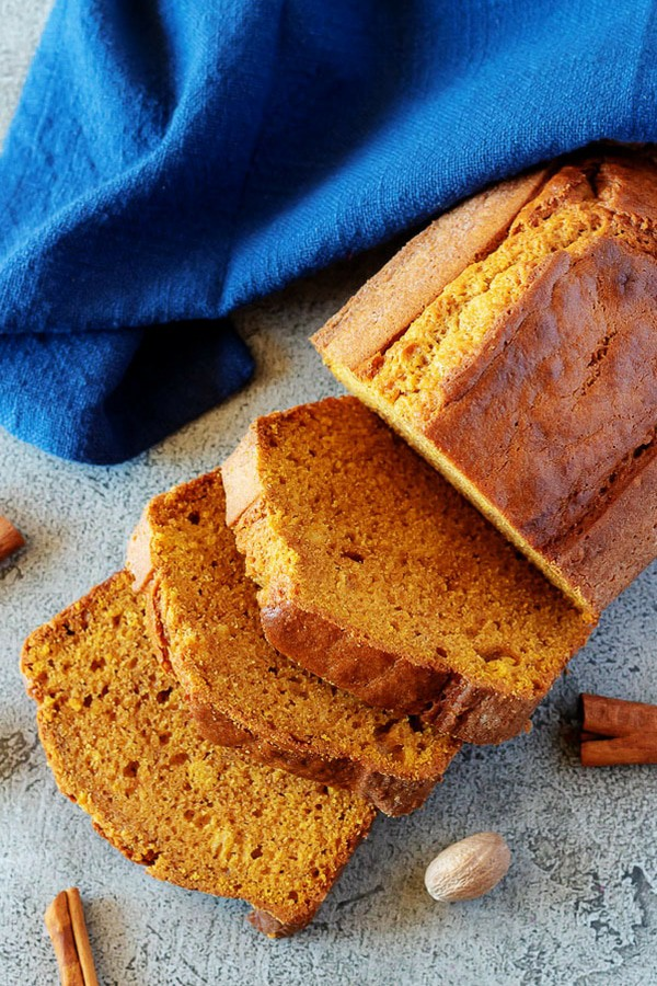 A large photo of the finished pumpkin bread recipe with three thick slices cut from the loaf.