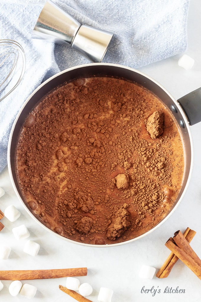 All of the spiked hot chocolate ingredients in a medium saucepan ready to be simmered.