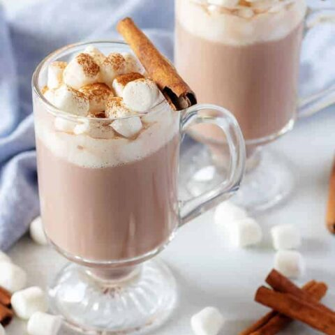 An angled view of the finished spiked hot chocolate in a glass mug and topped with mini-marshmallows.