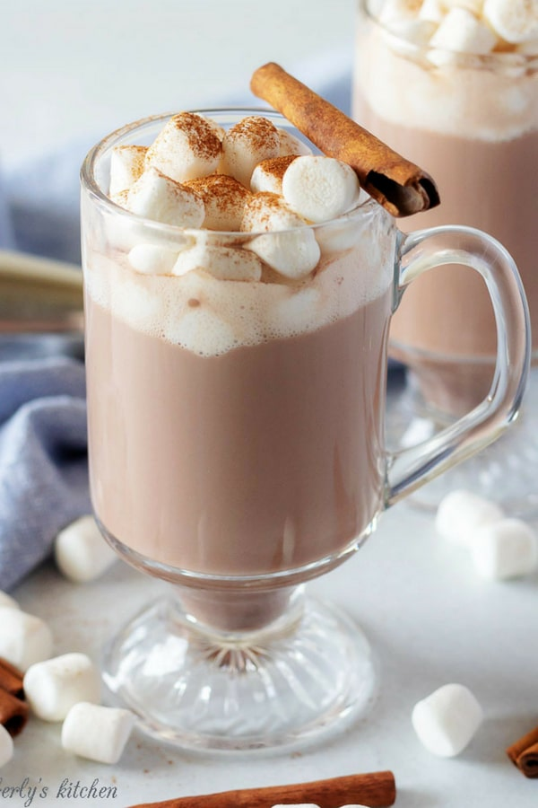 A large photo of the spiked hot chocolate in a clear mug, topped with marshmallows, and garnished with fresh cinnamon and a cinnamon stick.