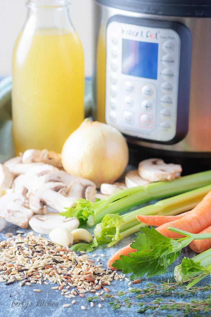 The instant pot soup ingredients like chicken broth, onions, carrots, and celery.