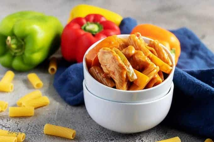 Chicken Fajita Pasta in stacked white bowls with bell peppers and a blue linen.