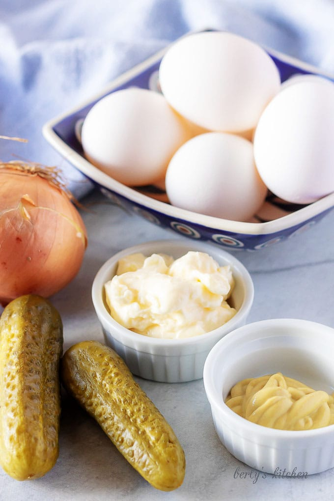 All of the easy deviled eggs ingredients like pickles, mayonnaise, mustard, and whit onion in bowl.