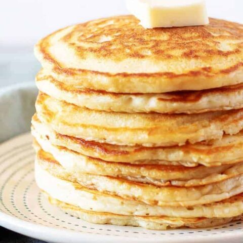 A simple photo of the finished fluffy american pancakes on a plate with butter.
